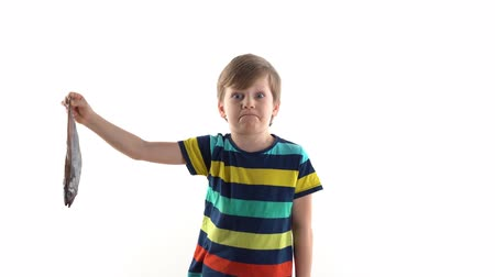 arenque : boy posing in studio on a white background with raw fish, grimaces of disgust Vídeos