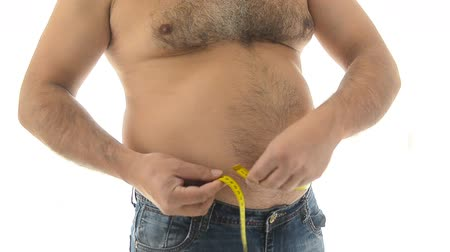 жир : Fat mature man measuring his belly with measurement tape.