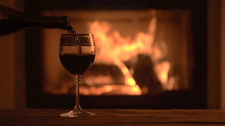 cozy : Pouring glasses of red wine by fireplace. Stock Footage