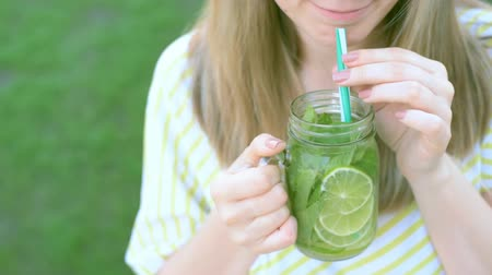 sparkling drink : Smiling girl drinking mojito in summer