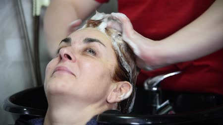 şampuan : A hairdresser washing hair of a woman with shampoo