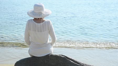 paraíso : Woman with a hat sitting on the rock on the beach meditating and relaxing Vídeos