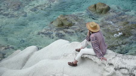 шляпа : Woman with a hat sitting on the rock near the sea meditating and relaxing Стоковые видеозаписи
