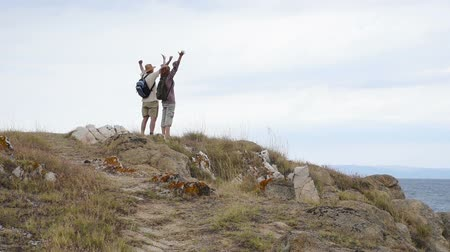 wspinaczka : Woman and man running on the mountain and showing hands up