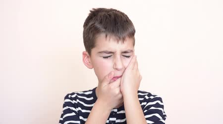 molar : Young boy with toothache holding his cheek