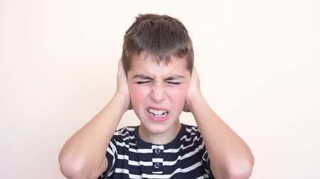 frustração : Young boy with closed eyes covering his ears with hands because of loud noise Stock Footage