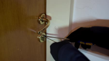 housebreaking : Robber with black gloves breaking the door lock. Focus on the keyhole. Stock Footage