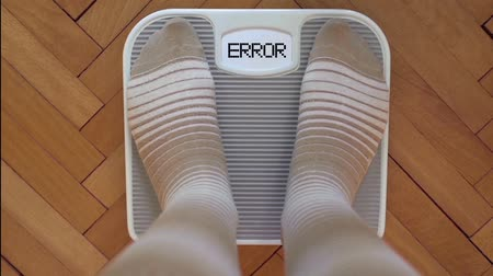 kilogramm : Person checking the weight on the scale. Display blinking ERROR. Stock mozgókép