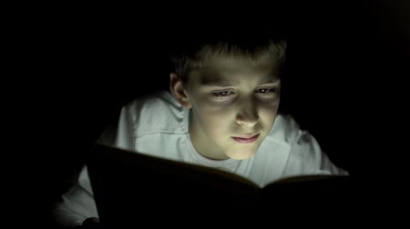 lanterna : Young boy reading a book hiding in the dark and using a torch light
