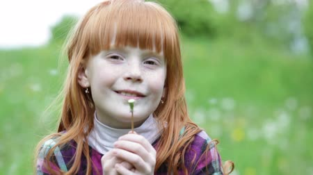 darbe : Close up little girls face blowing on a dandelion in the park, smiling Stok Video