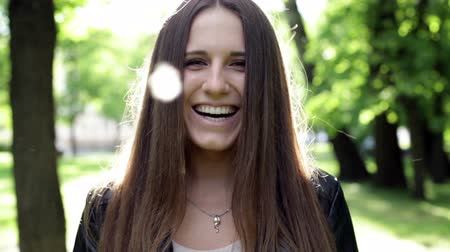 dış : Close up young smiling woman in a black coat, backlight, city park background Stok Video