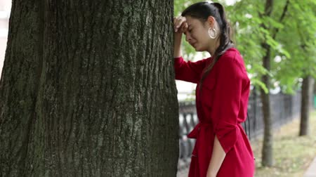 aflição : girl in a red dress crying near a tree