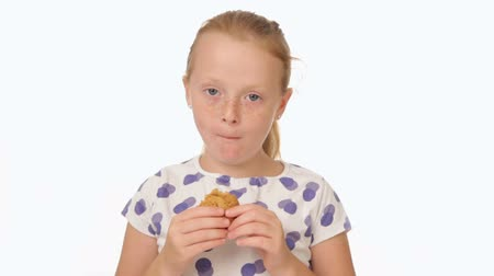 vöröshajú : little redhead girl eating a cookie Stock mozgókép