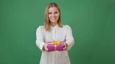 смеющийся : Young woman giving a gift and smiling, green screen background