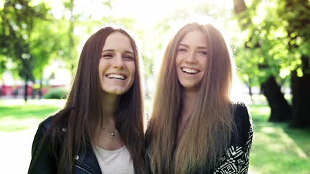 смеющийся : Close up two young laughing women in the city park
