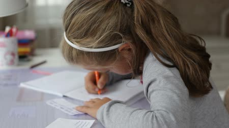 estudioso : Close up little girl writing something in an exercise book Stock Footage