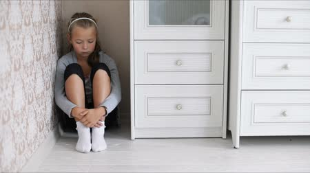 aggrieved : Little aggrieved girl sitting in the corner of a room hugging her knees