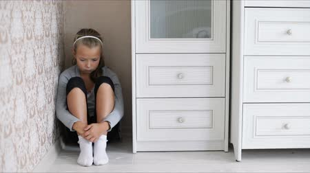 aggrieved : Little aggrieved girl sitting in the corner of a room on the floor hugging her knees Stock Footage