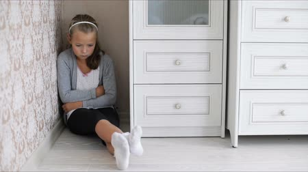 aggrieved : Little sad girl sitting in the corner of a room on the floor
