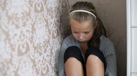 aggrieved : Little aggrieved girl sitting in the corner of a room with a sad face