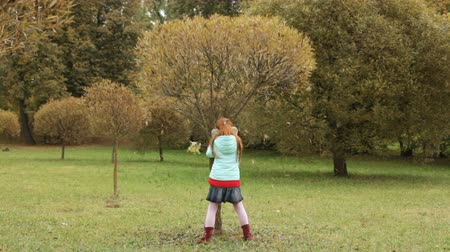 travessura : Little girl shaking a tree in the autumn park, leaves are falling