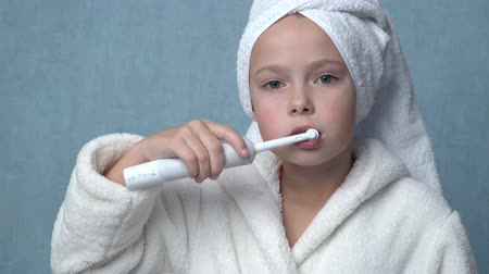 terry : Cute little girl in a towel and bathrobe cleaning teeth with electric toothbrush, blue background Stock Footage