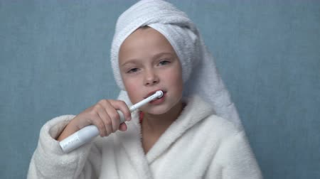 terry : Cute little girl in a towel and bathrobe cleaning teeth with electric toothbrush and smiling, blue background Stock Footage