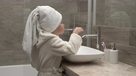 escovação : Little girl in a towel and a bathrobe cleaning teeth in the bathroom Vídeos