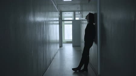 прихожая : Lonely woman standing in a dull corridor and writhing, touching the head in despair