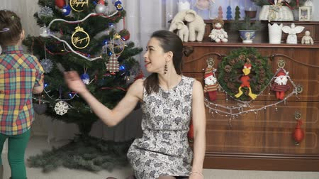 travessura : Young mother is playing with the daughter in a room with a dressed Christmas tree