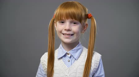 ruivo : Beautiful redhead girl with two pigtails looking onto the camera and smiling against gray background