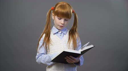vöröshajú : Beautiful redhead an a blue shirt and white vest is reading the book against gray background