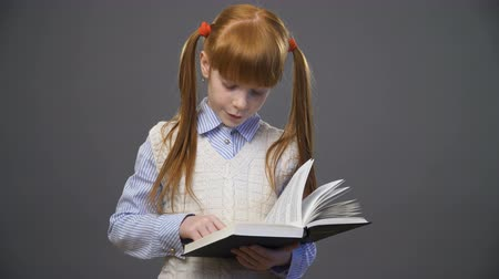 vöröshajú : Beautiful redhead girl an a blue shirt and white vest is reading the book, following the lines by the finger against gray background Stock mozgókép