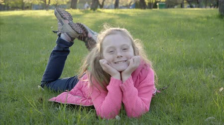 szeplők : Cute girl is lying on the grass in the park and smiling, backlight