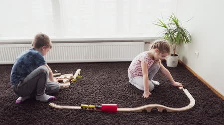 lokomotiva : Little boy and girl building a toy railway on the floor in a room Dostupné videozáznamy