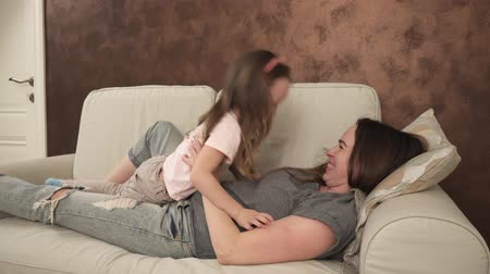 anne : Happy mother and little daughter embrace and tickle lying on the couch Stok Video