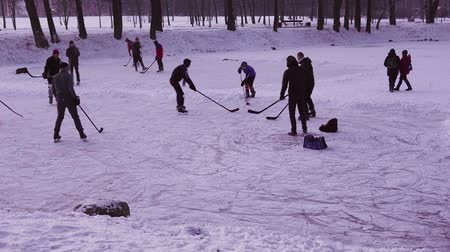 MINSK, BELARUS - JAN 23, 2018: Group of young people playing ice hockey on a frozen pond in a city park
