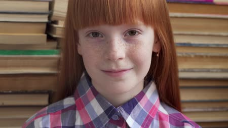 freckles : Close-up face of a little happy schoolgirl on background of books