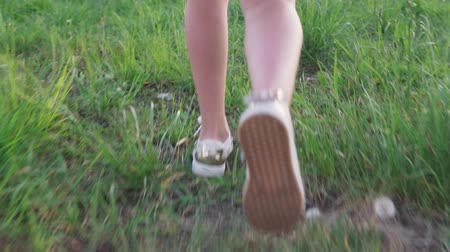 Legs little girl walking on grass Стоковые видеозаписи
