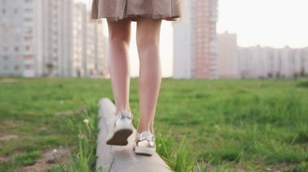 wasteland : Legs of little girl walking on concrete log on urban lawn Stock Footage