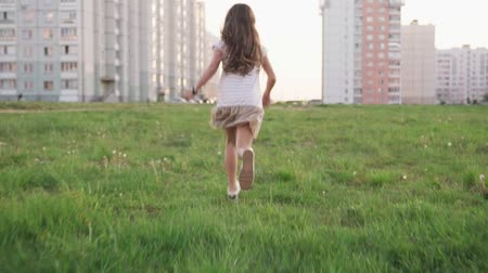 wasteland : Little girl running on grass on urban wasteland
