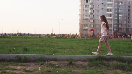 wasteland : Cute little girl walking on concrete log on city lawn Stock Footage