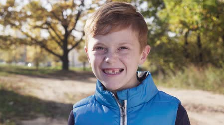 Happy little boy smiling without front primary tooth on sunny autumn day Стоковые видеозаписи