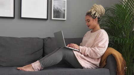 Young beautiful woman working on laptop and smiling on comfortable sofa at home Стоковые видеозаписи