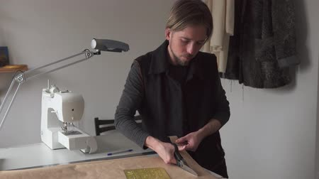 terzi : Man tailor with scissors cuts paper clothing pattern in workshop Stok Video