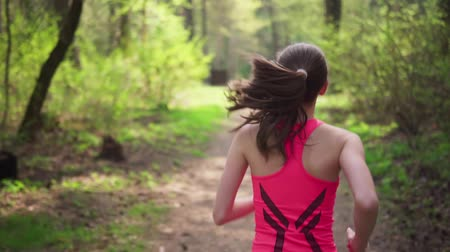 Active woman running in spring sunny forest Стоковые видеозаписи