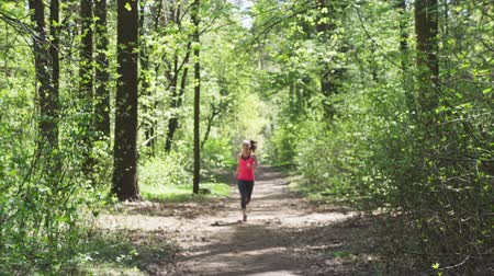 Fitness woman jogging in sunny forest