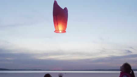 children launch sky lantern by sea at sunset