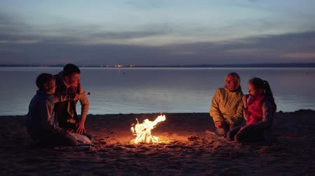 Family dinner by campfire on beach at night Стоковые видеозаписи