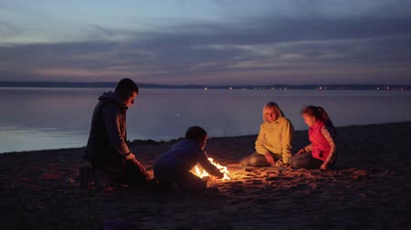 Family of tourists resting at campfire on night beach Стоковые видеозаписи